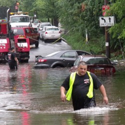 Towing service employees wade through flood waters to reach disabled cars on Amboy Road in Staten Island, N.Y., on Sunday, Aug. 14, 2011.