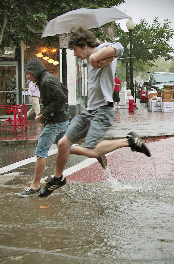 With lunch in hand, Zachary Cunha (right) and Nathan Grajales try to jump over the water running down William Street in downtown New Bedford, Mass., during a torrential downpour Monday, Aug. 15, 2011.