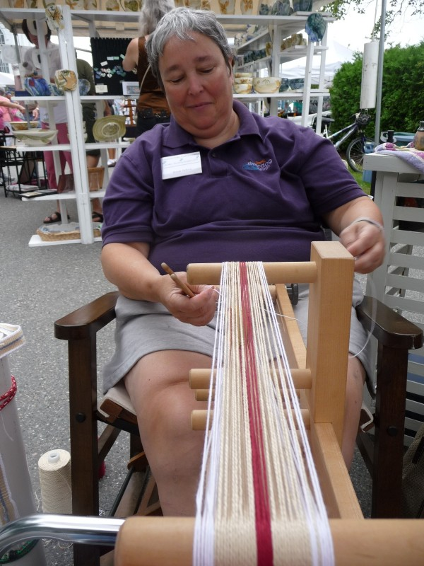 "Many of the vendors at this weekend's Wild Blueberry Festival at Machias demonstrated their skills for the thousands of visitors. Brenda Dalbeck of riverdog design fom West Gardiner weaves a cotton belt on an inkle loom. ""Oh, they're buying,"" Dalbeck said of the many visitors to the weeklong  festival. More than 250 vendors were on site all weekend. There were also blueberry pie eating contests, parades, a street dance, a fish fry, a musical play, blueberry farm tours, and the infamous Saturday night Black Fly Ball in Overlook Park at Bad Little Falls."