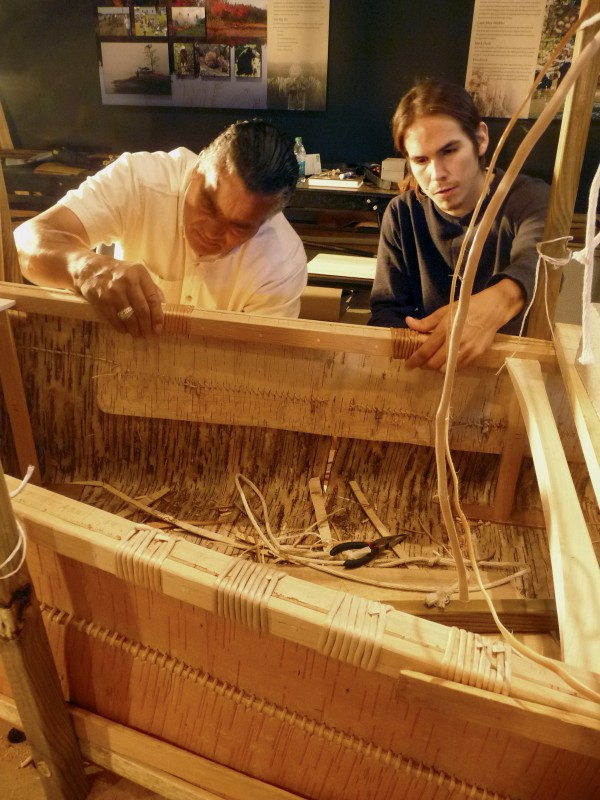 John Richardson (left) of Lancaster, PA., and Adam Perley, 20, of Tobique First Nation of New Brunswick, work on lashing the frame of the canoe.