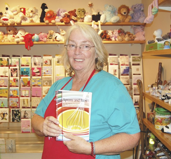 "Margaret Kiley, a maternity nurse who has worked at Pen Bay Medical Center for 27 years, proudly displays a copy of ""Aprons & Bibs,"" a new cookbook on sale in the renovated Pen Bay Gift Shop, which moved recently to a new location down the hall in the hospital. ""Aprons & Bibs"" contains 350 recipes from maternity nurses and others at Pen Bay, and is on sale at many locations in the community."