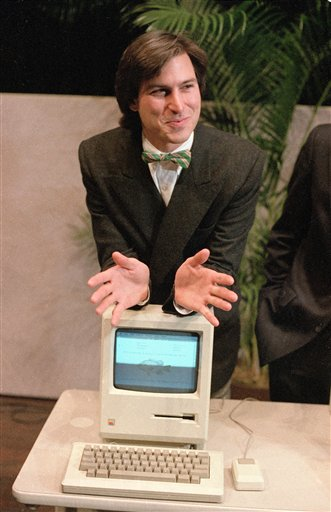 Steve Jobs, chairman of the board of Apple Computer, leans on the new Macintosh personal computer following a shareholder's meeting in Cupertino, Calif., in this Jan. 24, 1984 file photo.