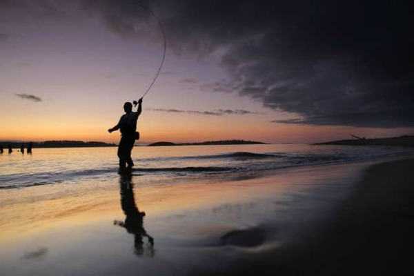 Fly-fisherman Bill Manser casts for striped bass at the mouth of Kennebec River at dawn on Aug. 5, while on vacation in Phippsburg, Maine. Americans need to relax more and take more vacation breaks, which promote good health and increase productivity. (Robert F. Bukaty / Associated Press)