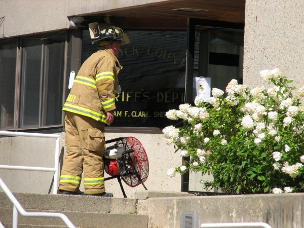 An Ellsworth firefighter sets up a fan outside the Hancock County Sheriff's Department entrance Tuesday morning after the smell of smoke was reported in the Hancock County Courthouse. The building was evacuated around 10:30 a.m. while Ellsworth firefighters investigated.