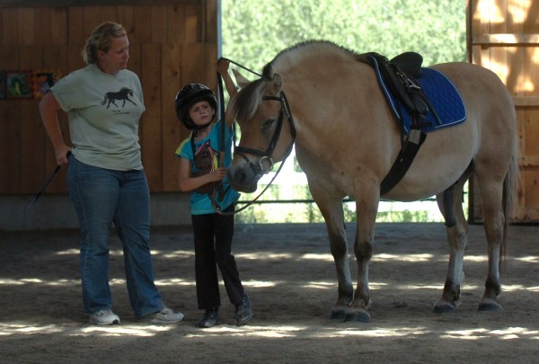 Respah Mitchell, left, of Hooves of Hope therapeutic riding program, oversees student Mercedes Severance, 7, of Carmel, during a lesson on Monday, August 1, 2011. Mitchell, an avid rider and special education teacher, runs the programs out of her Hermon horse farm.