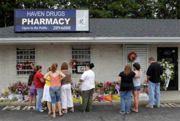 People gathered in front of the Haven Pharmacy in Medford, N.Y., where four people were killed, including two employees and two customers, during a shooting on June 19, 2011, during a holdup for prescription painkillers.