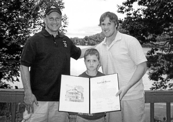 Jimmy Howard (right), Detroit Red Wings goalie and former University of Maine hockey player, receives a Legislative Sentiment honoring his success in college and pro hockey, and his work supporting local hockey programs for youngsters. Presenting the honor are Chris Greeley (left), former state representative from Levant, who sponsored the measure while in the Legislature; and his son Cole Greeley, 7, member of the Brewer Mites. Howard lives in Michigan and Maine.
