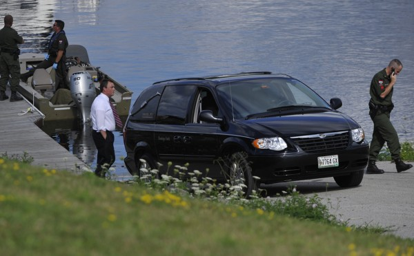 A hearse is parked at the bottom of a boat ramp on the Penobscot River near the Hampden-Bangor line as Maine wardens and local police confer after a body was recovered from the river Friday afternoon, August 5, 2011. The two-day search for Judy Markowsky concluded with somber news Friday when her body was found in the river.