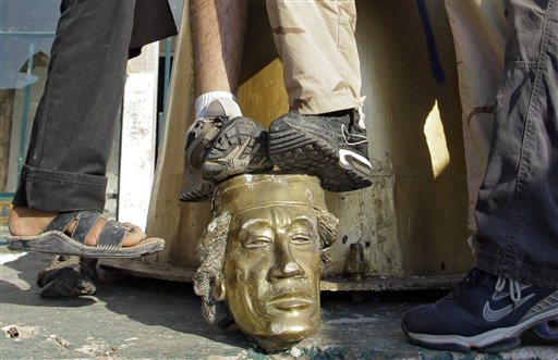 Rebel fighters trample on a head of Moammar Gadhafi inside the main compound in Bab al-Aziziya in Tripoli, LIbya, Tuesday, Aug. 23, 2011.