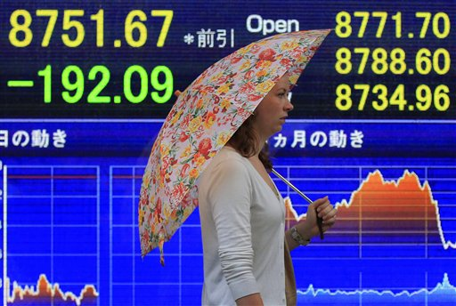 A woman walks in front of the electronic stock board of a securities firm in Tokyo Friday, Aug. 19, 2011. Asian stock markets were sharply lower Friday amid signs of a possible U.S. recession and renewed worries over the health of Europe's banks.