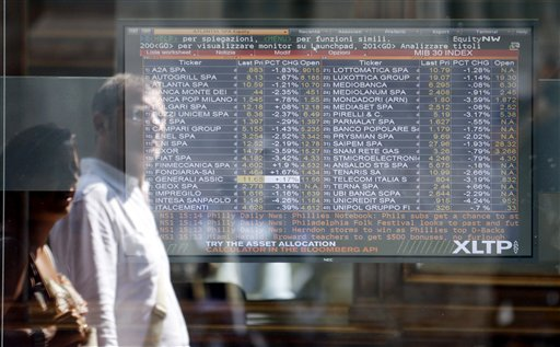 A couple is reflected in a bank stock market monitor in downtown Milan, Italy. Global stocks were mixed Monday over fears of a possible U.S. recession combined with ongoing worries over Europe's debt crisis.
