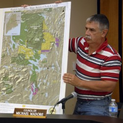 Councilor Michael Madore holds a map illustrating environmentalist Roxanne Quimby's land holdings during a meeting on Thursday, July 28, 2011.