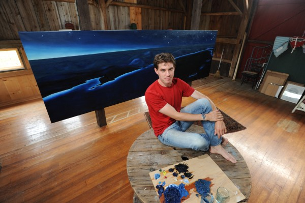 Orlando Johnson in his studio on North Haven on Thursday, July 21, 2011 with one of his recent painting depicting an aerial view of the Rockland/Camden coastline.