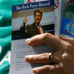 A supporter of Republican presidential candidate former Minnesota Gov. Tim Pawlenty holds a flyer about Texas Gov. Rick Perry at the Republican Party's Straw Poll in Ames, Iowa, Saturday, Aug. 13, 2011.