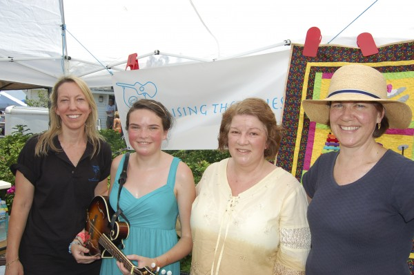 Bethany Schulberg (second from left) was presented with a brand new mandolin during the North Atlantic Blues Festival in Rockland on July 17. Ruth Atherton (left) is the founder of the charitable organization Raising the Blues, which donated the instrument and music lessons to Bethany. At right are Bethany's mother Cinda Shulberg and Penney Read, vice president of Pen Bay Healthcare Foundation.