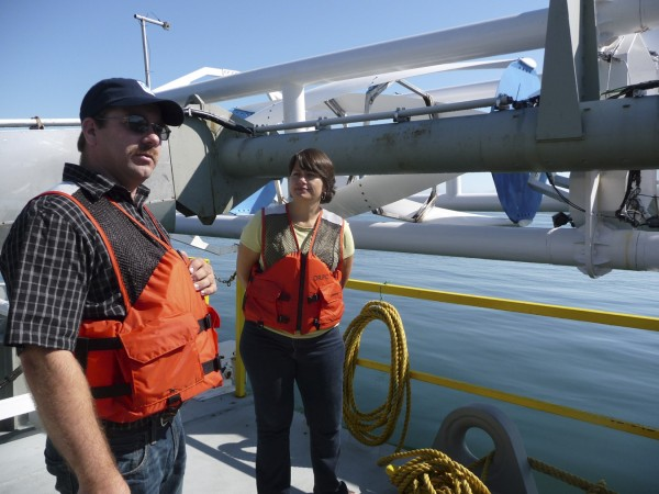 "Project Manager David Turner and Ocean Renewable Power Company spokeswoman Suzy Kist explain how the company's 40-foot, 37,000 pound hydro-turbine works Friday during an open house on the ORPC barge in Eastport. ""Eastport is the epicenter of tidal energy in the U.S.,"" Kist said."