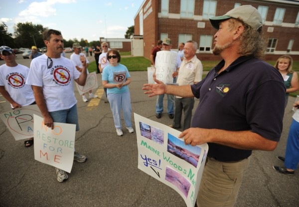 Mike Mayhew of Boothbay Harbor, right, argues the merits of having a national park in northern Maine with Millinocket resident Jim Busque, left, in front of Stearns High School in Millinocket on Thursday, Aug. 18, 2011 before Interior Secretary Ken Salazar was to hear public comment on the proposed park.