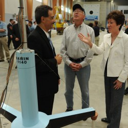 Secretary of the Interior Ken Salazar (center) looks up at a model of a floating windmill as Advanced Wood Composites Center director Habib Dagher (left) explains the model to Salazar and Sen. Susan Collins (right) on Thursday, August 18, 2011 in Orono.