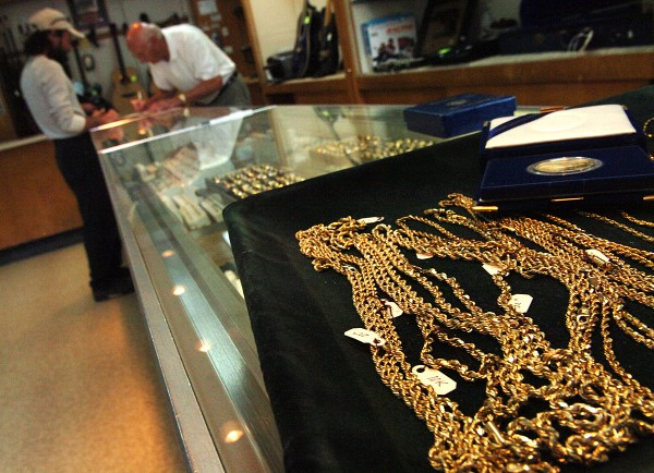 "Amidst displays of gold jewelry, Orlando Frati Sr. (right) helps a customer on Monday, Aug. 15, 2011, at his business, Frati's Pawn Shop in Bangor. ""We've had a lot of people looking to buy and sell because the price is up so high,"" said Frati of the recent soaring gold prices."