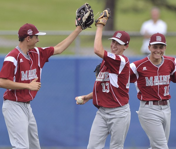 Brewer center fielder Jeremy Bissell (center) is congratulated by teammates Jeff Weeks (left) and Ben Pushard (11) after making a diving catch for the final out in the Maine District 3 champion's 7-2 win over Canada in opening-day play at the Senior League World Series at Mansfield Stadium in Bangor on Sunday.