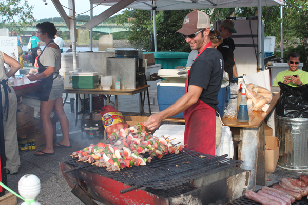 Nalbert Tero grills lamb and vegetable kabobs from The Noon Family Sheep Farm Lamb Barbecue at the American Folk Festival Saturday, Aug. 27, on the Bangor Waterfront.