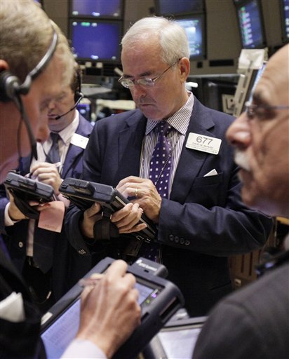David McHugh, center, works with fellow traders on the floor of the New York Stock Exchange. Stocks turned higher Friday after Federal Reserve Chairman Ben Bernanke spoke optimistically about long-term prospects for the U.S. economy.