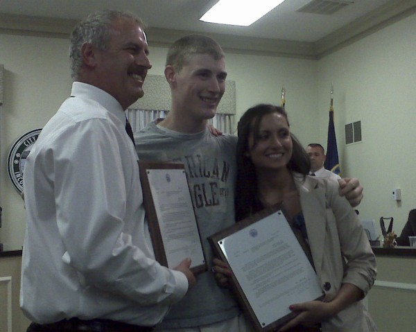 Two young adults, Tyler Eagan and Amber Cates, were honored by the Brewer City Council for saving a person who drove into the river on July 5. City Council member Kevin O'Connell (left) presents the duo with plaques in honor of their actions.