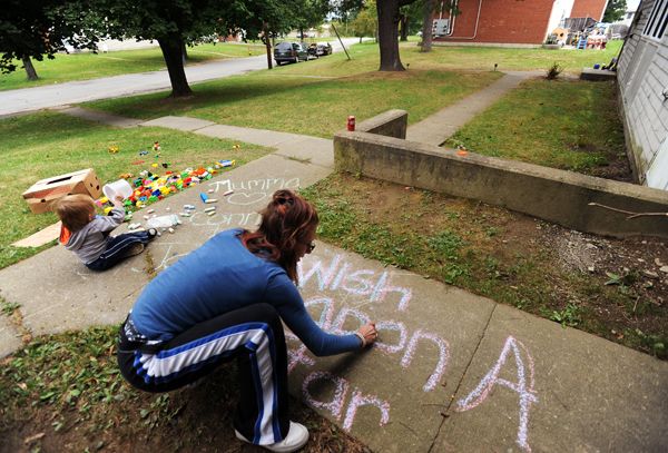 Mindy Iwaniszek of Bangor writes &quotwish upon a star&quot in chalk on the walkway to her Mitchell Street home she shares with her children, Connor and Jordan, in September 2010. Iwaniszek is a recipient of general assistance from the city of Bangor.