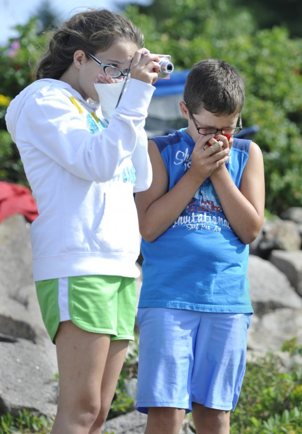 Haley Miller, 15, and her brother Dakota, 10, of Winterport cover their noses as the aroma of the beached dead minke whale wafts in the air while local researchers dissect it at Otter Cove on Wednesday afternoon, August 24, 2011.