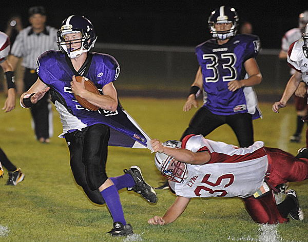 John Bapst High School's Andew Catlin (left) breakes a takle by Mattanawcook Academy's A.J. MacEachern during the second quarter Friday night at Cameron Stadium. The game was suspended after the lights went out with Bapst leading 25-6.