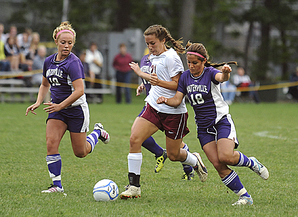 Bangor High School's Ashley Robinson drives toward the goal between Waterville's Lauren Massey (right) and Melanie Bureau to score Bangor's first goal during the first half of the game Tuesday evening. Bangor won 8-0.