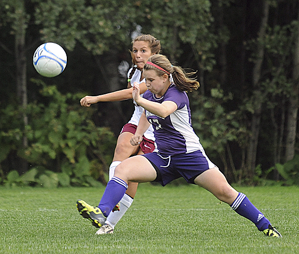 Bangor High School's Ashley Robinson (left) passes the ball down the field past Waterville's Cassidy Dangler during the first half of the game Tuesday evening.