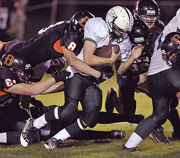 Brewer's Matt Cuskelly (8) and Josh Lugdon (61) bring down a determined Dan Rivers (47) of Old Town in their game at Doyle Field in Brewer Friday, Sept. 9, 2011.