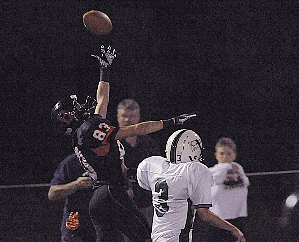 Brewer's Ryan Miller (83) leaps but can't come up with the ball on a deep pass under pressure form Old Town's Cameron Archer (3) in the final minutes of the second quarter of their game at Doyle Field in Brewer, Friday Sept. 9, 2011.