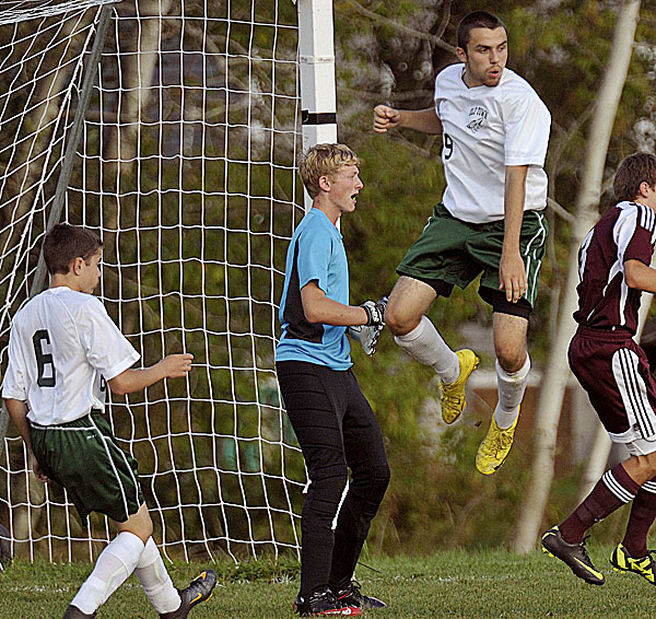 Old Town's Matt Melanson (9) tries to work a deflection with teammate Travis Chappelle (6) past Ellsworth's keeper Steven Mahon in the second half of their game in Old Town, Monday Sept. 12, 2011. Ellsworth won 5-1.