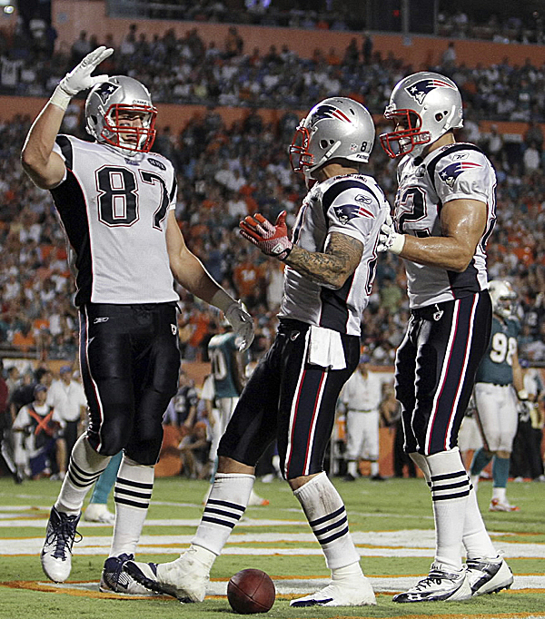 Rob Gronkowski (left) congratulates fellow tight end Aaron Hernandez (center) after Hernandez scored in Monday night's game in Miami against the Dolphins. The Patriots defeated the Dolphins 38-24.