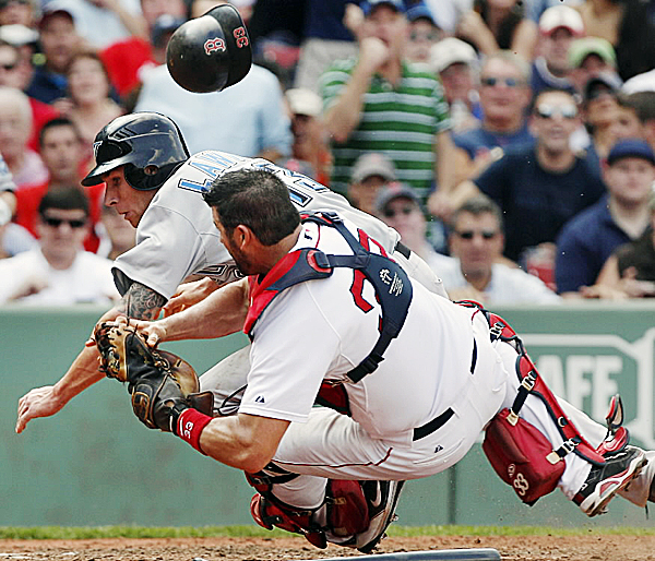 Boston Red Sox catcher Jason Varitek loses his helmet but hangs onto the ball as the Toronto Blue Jays' Brett Lawrie barrels into him. Lawrie unsuccessfully tried to score on a fielder's choice during the sixth inning of Wednesday's game at Fenway Park in Boston. The Blue Jays won 5-4.