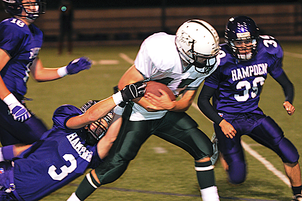 Old Town's Dan Rivers breaks tackles as he advances up the field against Hampden's Matt Haws (left) and Ryan Faircloth (39) on Friday, September 16, 2011 at Hampden. Hampden won 62-30.