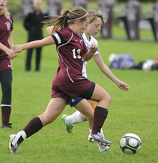 Mattanawcook Academy's Ashley Crashy (left) and John Bapst High School's Jessica Moore  go after the ball during the first half in Bangor Tuesday evening.