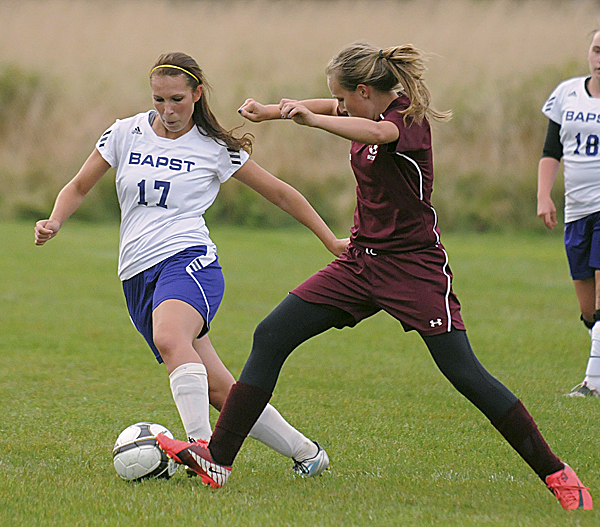 John Bapst High School's Laine Ferrill (left) and Mattanawcook Academy's Katie Krapf  battle for the ball during the first half of the game in Bangor Tuesday evening.