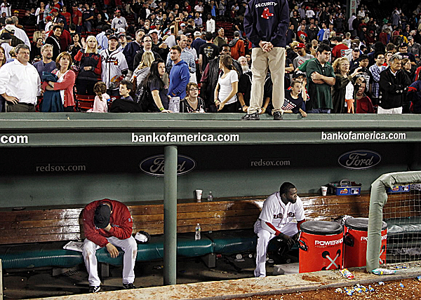 Baseball fans stand to leave Fenway Park as Boston Red Sox relief pitcher Alfredo Aceves, left, and designated hitter David Ortiz react as they linger in the dugout after they were defeated 6-4 by the Baltimore Orioles in a baseball game at Fenway Park in Boston, Wednesday night, Sept. 21, 2011.