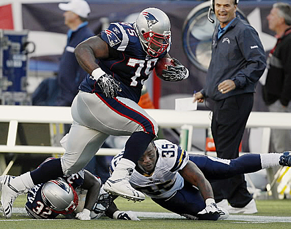New England Patriots nose tackle Vince Wilfork (75) runs over cornerback Devin McCourty (32) with the football after intercepting a pass as San Diego Chargers running back Mike Tolbert (35) reaches out to bring him down in the second quarter of an NFL game in Foxborough, Mass., Sunday, Sept. 18, 2011.