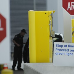Viewed from the Canadian side of the border, A U.S. port of entry officer carefully checks a motorist's identification at the Jackman port of entry in Sandy Bay Township on Aug. 18, 2011. Maine's border security has changed since the September 11, 2001 attacks.