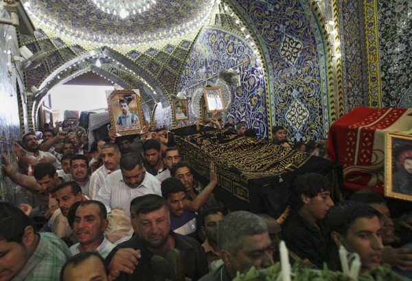Mourners carry the coffins of slain Shiite pilgrims during their funeral in the holy city of Karbala, 80 kilometers (50 miles) south of Baghdad, Iraq, Tuesday, Sept. 13, 2011. The victims were killed when gunmen forced their way onto a bus of traveling Shiite pilgrims Monday and shot all 22 men onboard as they traveled through western Iraq's remote desert on a trip to a holy shrine, security officials said.