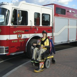 "Adam MacDonald, 25, of Presque Isle, is enjoying volunteering with members of the Bangor Fire Department for their International Fire Fighters Association Muscular Dystrophy Association ""Fill the Boot"" campaign as the local fire fighters seek donations during the Bangor Waterfront Concert Series."