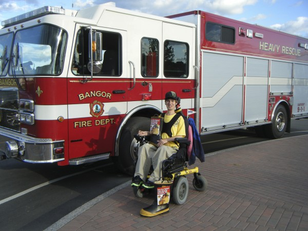 Adam MacDonald, 25, of Presque Isle, is enjoying volunteering with members of the Bangor Fire Department for their International Fire Fighters Association Muscular Dystrophy Association &quotFill the Boot&quot campaign as the local fire fighters seek donations during the Bangor Waterfront Concert Series.