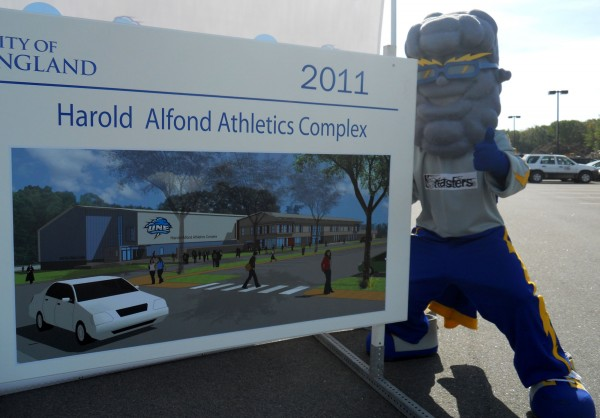 """Stormin' Norman"" the University of New England's sports mascot, poses for a picture alongside an architect's rendering of the new $20 million Harold Alfond Athletics Complex, currently being built on the school's Biddeford campus. On Monday, UNE officials were joined by members of the public, student athletes and representatives of the Harold Alfond Foundation to for a ceremony to celebrate construction."