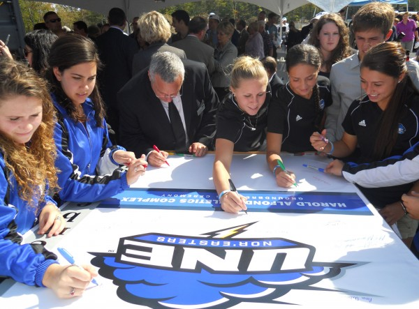 Student athletes and dignitaries in attendance at a Monday ceremony celebrating University of New England's new sports complex sign a banner commemorating the event.