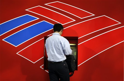 In this July 17, 2009 file photo, a customer uses a Bank of America ATM in Charlotte, N.C.  Bank of America plans to start charging customers a $5 monthly debit card fee. The fee will be rolled out starting early in 2012. (AP Photo/Chuck Burton, file)