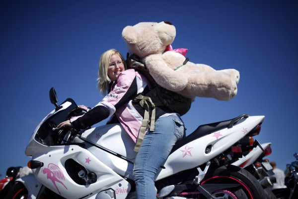 Katrina Tong of Augusta poses with the large stuffed bear she donated following the 30th annual toy run to be given to children throughout the state at Christmas.